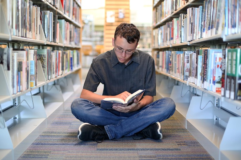 senior boy reading book in isle of library